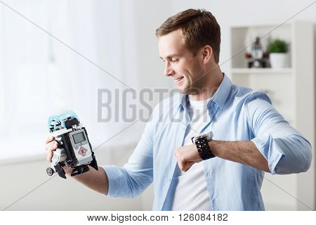 Modern invention. Cheerful handsome delighted man smiling and using robot while expressing gladness