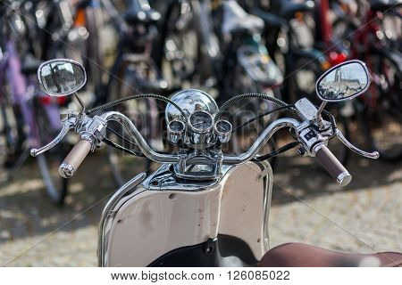 handlebar with chrome instruments and headlight of a scooter