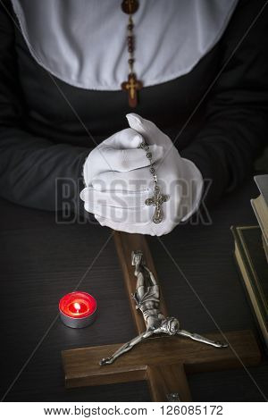 Priest praying a rosary, burning candle, religious concept