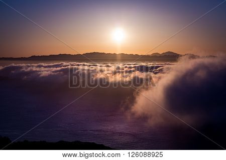 dramatic sunset above the fog over the San Francisco Bay