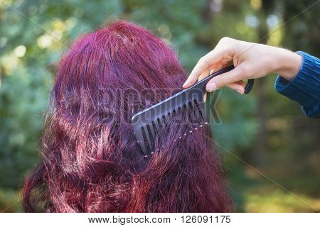 In sun light girl's hand with black comb combing woman's red hair