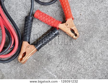 Black and red copper clamp with jumper cable for car battery charging selective focus