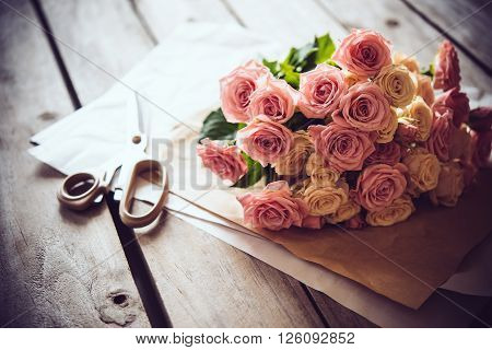 Florist's workspace: bouquet of fresh roses and scissors on an old vintage wooden board table.