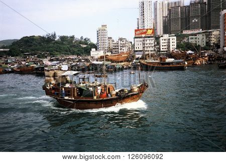 ABERDEEN / HONG KONG - CIRCA 1987: A houseboat enters the harbor at the Aberdeen Floating Village in Hong Kong.