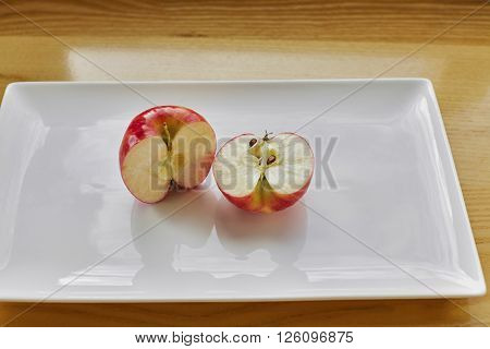Red Apple Cut In Half On White Plate