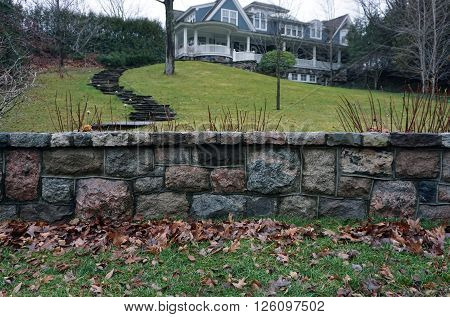 A stone wall stands in front of a large lakefront mansion on a hilltop along Glenn Drive in Harbor Springs, Michigan.