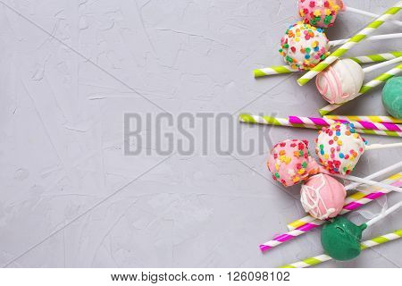 Party background. Colorful cake pops and paper straws on grey textured background. Selective focus. Place for text.