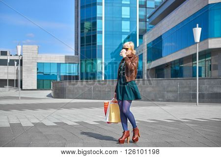 Beautiful woman in sunglasses drinking coffee with shopping bags on the street