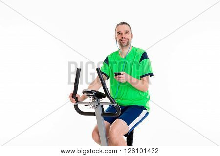 young man in green shirt train with fitness machine and listening music
