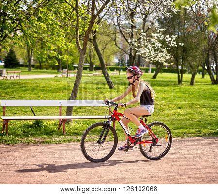 Bikes cycling girl wearing helmet riding on bicycle lane.