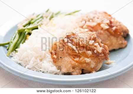 cripsy fried chicken thighs with vegetables over rice in a lemon sauce ** Note: Shallow depth of field
