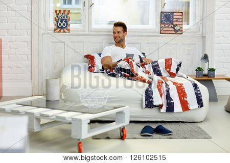 Happy young man smiling in bed, holding morning tea, looking away.