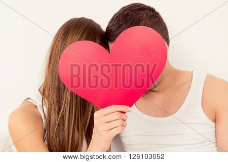 Close Up Portrait Of Two Lovers Hiding Faces Behind Big Paper Heart