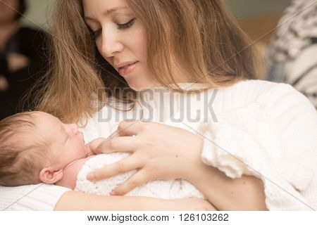 Cute infant on the hands of mother