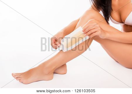 Close Up Photo Of Woman Using Beeswax Stripe To Shave Her Leg