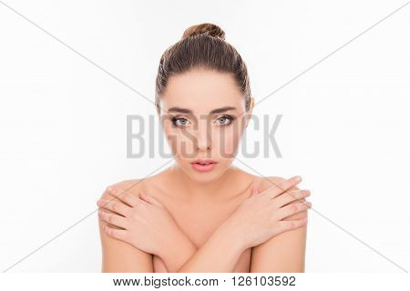 Beautiful tender young woman posing with crossed hands and touching her shoulders