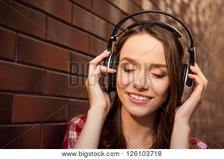 Close up portrait of young cheerful girl listening music with headphones