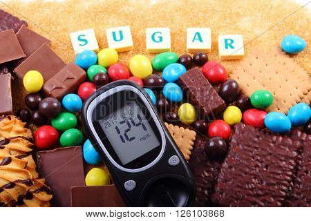 Glucometer with word sugar heap of candies cookies and brown cane sugar too many sweets unhealthy food concept of diabetes and reduction of eating sweets