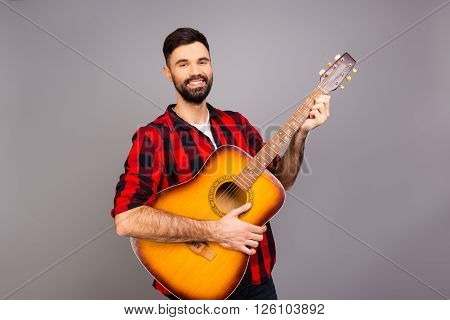Portrait Of Young Successful Musician Holding Guitar And Smiling