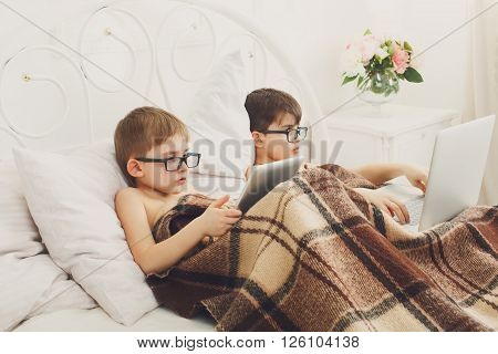 Two children, boys in parents' bed at morning with laptop and tablet. Brothers play computer games. Siblings and gadgets. Boys in eyeglasses. Children and computer glasses.