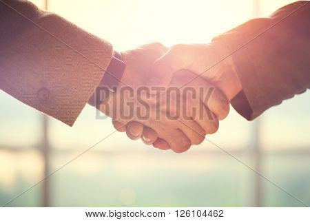 Business handshake. Business handshake and business people concept. Two men shaking hands over sunny office background. Partnership, Deal