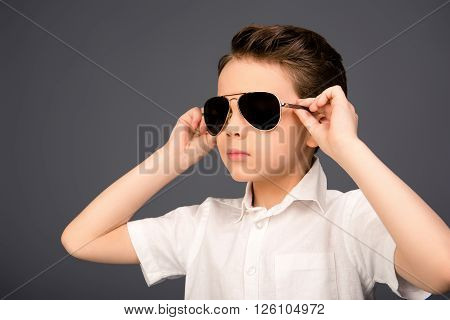 Portrait Of Serious Cool Kid Touching His Spectacles
