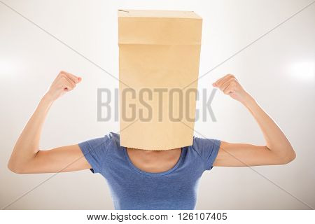 Girl with bag covering her head and showing her biceps