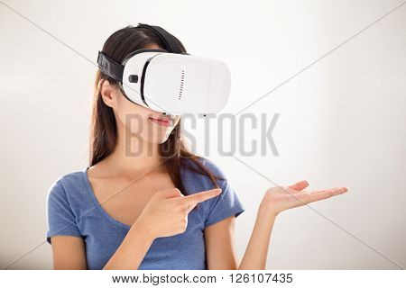 Woman using virtual reality and hand showing copy space