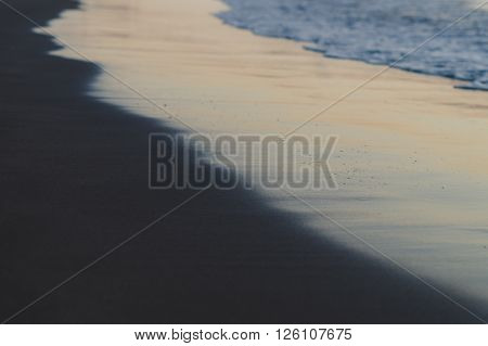 Blurred background of waves and black sand beach on sunset