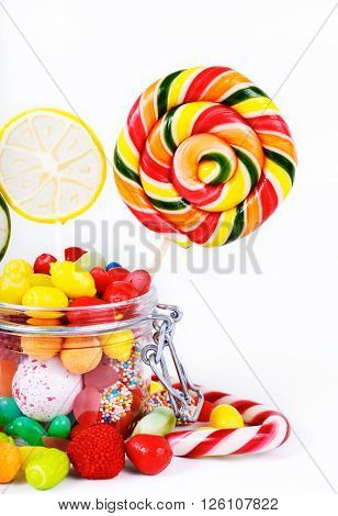multicolored lollipops candy and chewing gum in the jar of glass closeup on a white background