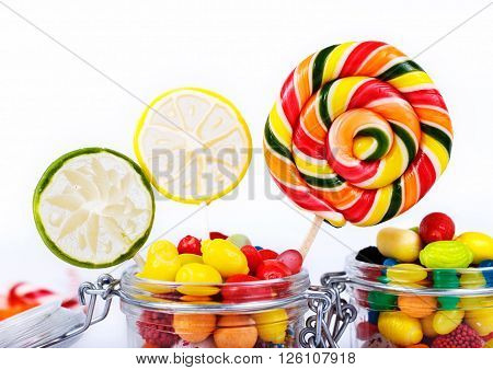 Colorful candies sweetmeats and chewing gum in the glass jar closeup on a white background
