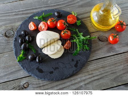mozzarella cheese with cherry tomatoes arugula and black olives on a ceramic board on wooden table top view