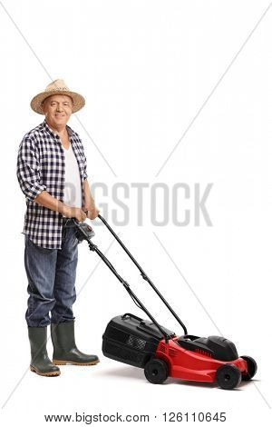 Vertical shot of a mature man posing with a red lawn mower isolated on white background
