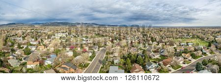aerial panorama of Fort Collins in northern Colorado - residential buildings with Rocky Mountains foothills in background, early spring scenery