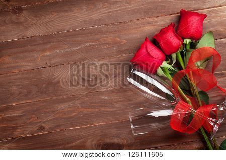 Red roses and champagne glasses over wood with copy space. Valentines day background