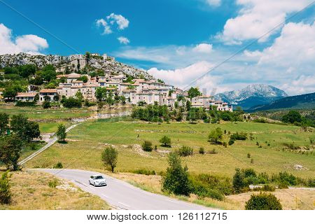 Car Goes On Road Against Background Of Beautiful Scenic View Of Medieval Hilltop Village Of Trigance In Provence, Cote De Azur, France