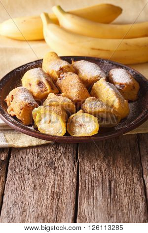 Tasty Fried Bananas In Batter With Powdered Sugar. Vertical