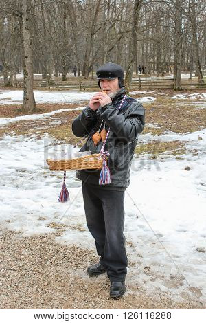 Vitoslavlitsy, Russia - 12 March, Buffoon playing the penny whistle, 12 March, 2016 Feast Maslenitsa in the museum of wooden architecture