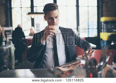 Single Man Drinking Coffee And Reading Newspaper In Cafe