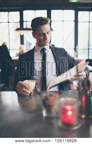 Single Young Man In Suit Reading Newspaper In Bar
