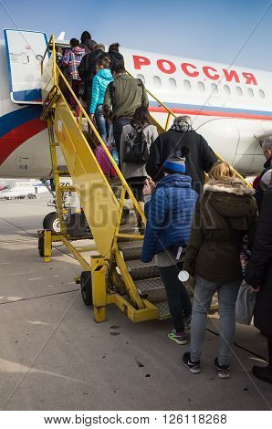 Saint-Petersburg Russia - November 5 2015: Landing of ordinary passengers on a plane of Russian Airlines company on yellow ramp
