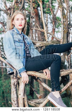 Fashionable blonde is sitting in torn jeans