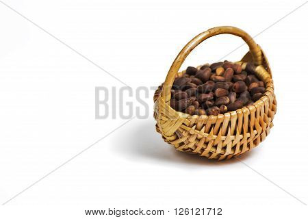 Bast basket with pine nuts on a completely white background.