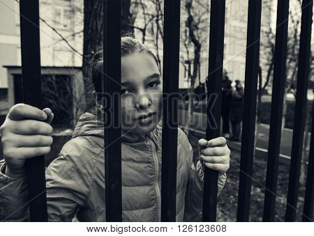 Sad girl holding grille and look out side freedom.