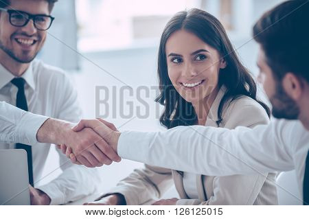 Business handshake. Close-up of two young man shaking hands with smile while sitting at office with their beautiful coworker