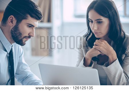 We need to read our contract once again. Close-up of beautiful young businesswoman looking at her laptop while sitting at the office table with her coworkers