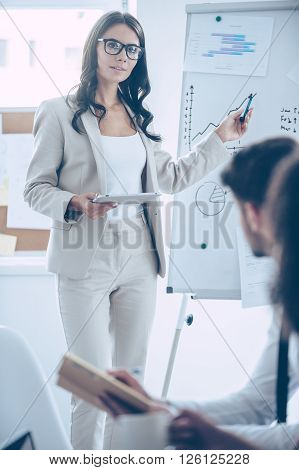 We should focus on these numbers! Young beautiful woman pointing at whiteboard and discussing something with her coworkers while standing in office