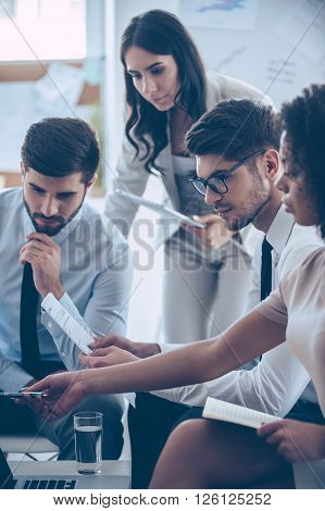 Take a look at this numbers! Young beautiful African woman pointing at her laptop while sitting on the couch at office with her coworkers