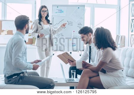 We can see growth here! Young beautiful cheerful woman pointing at whiteboard and discussing something with her coworkers with smile while standing in office