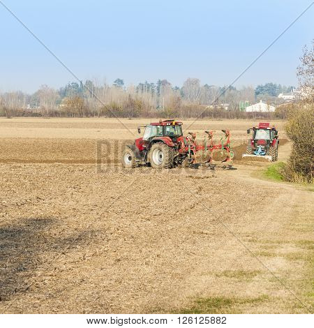 Agricultural labor Red Tractor plowing a field